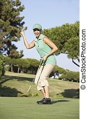 Female Golfer On Golf Course Putting On Green