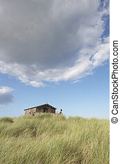 Distant View Of Young Couple Relaxing In Wooden Beach Hut...