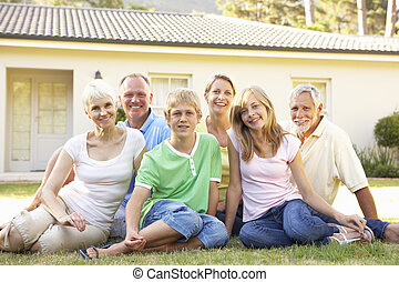 Extended Family Sitting Outside Dream Home