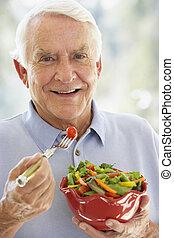 Senior Man Smiling At Camera And Eating Salad