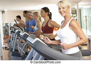 Senior Woman On Running Machine In Gym