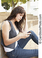Unhappy Female Teenage Student Sitting Outside On College Steps Using Mobile Phone