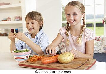 Happy children peeling vegetables in kitchen