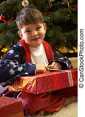 Young Boy Opening Christmas Present In Front Of Tree