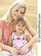 Mother And Daughter Sitting On Straw Bales In Harvested...