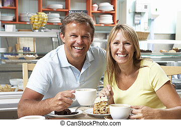 Couple Enjoying Slice Of Cake And Coffee In Caf