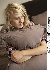 Depressed Teenage Girl Hugging Pillow In Bedroom