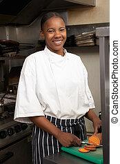 Female Chef Preparing Vegetables In Restaurant Kitchen