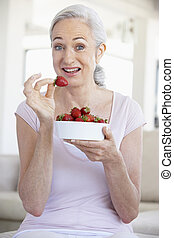 Senior Woman Eating A Bowl Of Strawberries