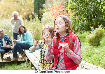 Two Young Girls Blowing Bubbles On Countryside Picnic