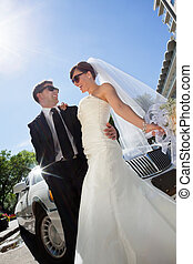 Happy Wedding Couple with Limo