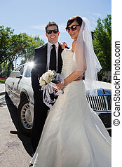 Newly wed couple in sunglasses standing near limousine