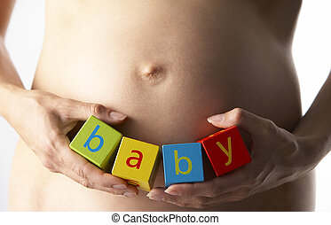 Pregnant Woman Holding Blocks Spelling Baby