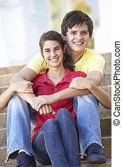 adolescente, pareja, Sentado, en, colegio, pasos, exterior