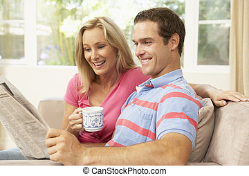 Couple Reading Newspaper At Home