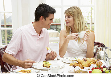 Young Couple Enjoying Hotel Breakfast