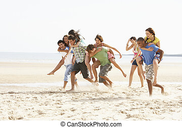 Group Of Friends Running Along Beach Together