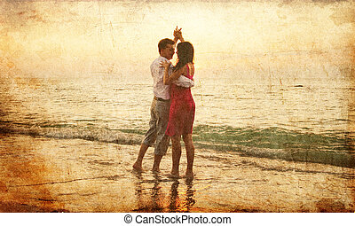 Couple dancing at the beach in sunset.