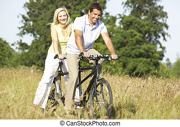 Couple riding tandem in countryside