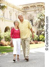 Senior Couple Walking Through City Street