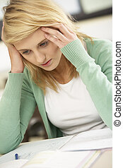 Stressed Female Teenage Student Studying In Classroom
