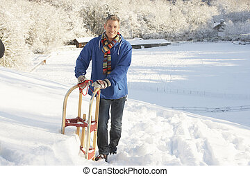 Middle Aged Man Standing In Snowy Landscape Holding Sledge