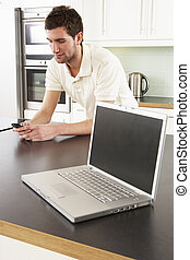 Young Man With Laptop In Modern Kitchen
