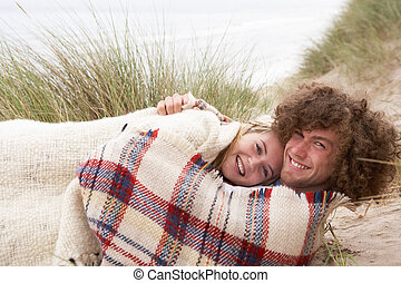 Teenage Couple Sitting In Sand Dunes Wrapped In Blanket