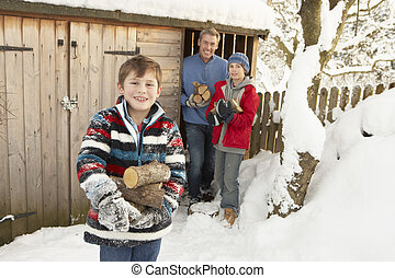 Family Collecting Logs From Wooden Store In Snow