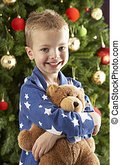 Young Boy Cuddling Teddy Bear In Front Of Christmas Tree
