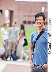 Portrait of a handsome student posing while his classmates are talking in a yard