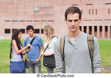 Lonely student posing while his classmates are talking...