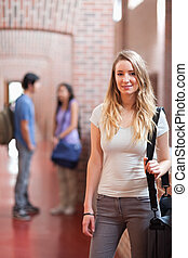 Portrait of a student posing while her friends are talking