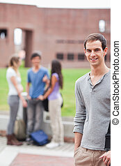 Portrait of a male student posing while his classmates are talking in a yard