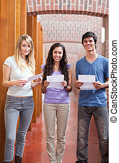 Portrait of smiling students holding a piece of paper