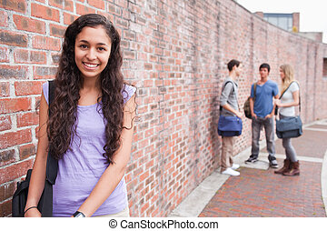 Smiling student posing while her friends are talking