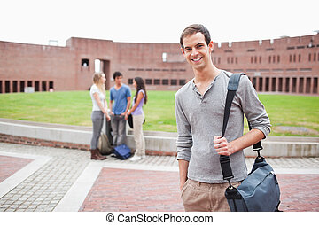 Student posing while his classmates are talking