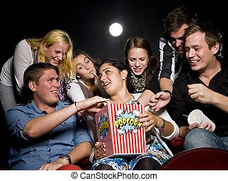 People eating popcorn - Group of young spectators eating...