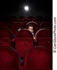 Afraid young man alone in the movie theater