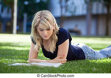 Girl reading book - Pretty female reading book while lying...