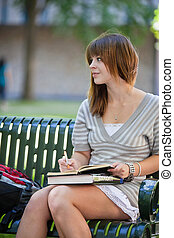 College Girl Studying - Young college girl sitting on bench...