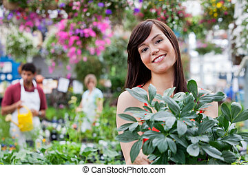 Attractive female customer holding potted plant