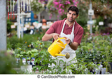 Young Man Watering Plants - Portrait of young man watering...
