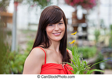 Smiling woman holding flower pot