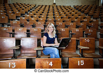 Woman Student in Empty Lecture Hall - Portrait of young...