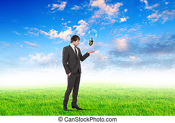 Young businessman outdoor with a bulb as a symbol of...
