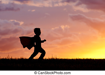Boy plays super hero at sunset. - A young boy wearing a cape...