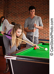 Portrait of young friends playing snooker
