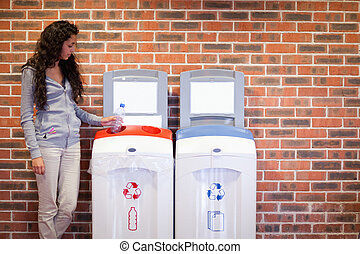Young woman recycling a plastic bottle