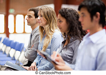 Business people listening and taking notes during a...
